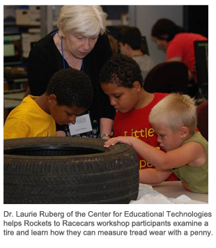Dr. Laurie Ruberg of the Center for Educational Technologies helps Rockets to Racecars workshop participants examine a tire and learn how they can measure tread wear with a penny.