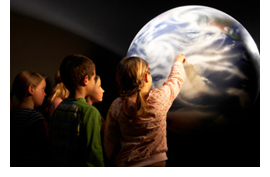 Image of some students pointing to a map of the Earth.