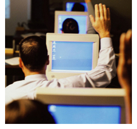 Image of serveral adult students raising their hands while sitting at individual computers.
