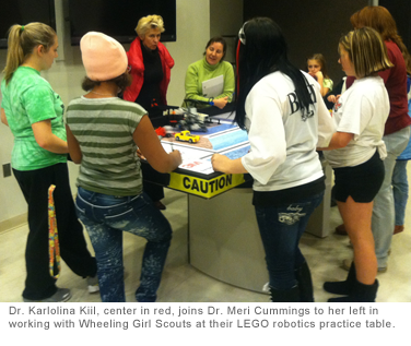 Dr. Karlolina Kiil, center in red, joins Dr. Meri Cummings to her left in working with Wheeling Girl Scouts at their LEGO robotics practice table.