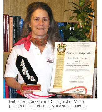 Image of Debbie Reese holding Distinguished Visitor proclamation.